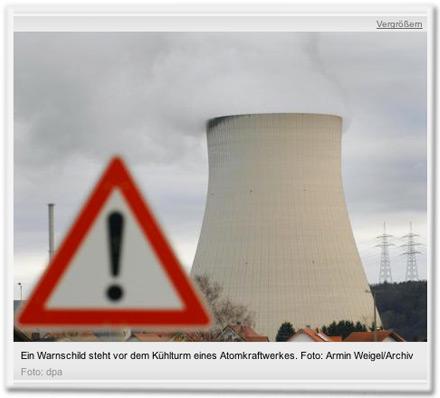 Ein Warnschild steht vor dem Kühlturm eines Atomkraftwerkes.