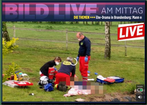 Screenshot Bild.de - Bild live am Mittag - Die Themen - Ehe-Drama in Brandenburg - dazu ist ein Standbild einer Szene zu sehen, in der mehrere Rettungskräfte über einer Person, die am Boden liegt, knien.