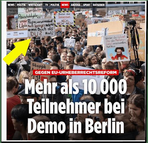 Screenshot Bild.de - Gegen EU-Urheberrechtsreforn - Mehr als 10000 Teilnehmer bei Demo in Berlin - erneut der erste Ausriss mit dem Foto, das Demonstranten in Berlin zeigt, die beschriftete Schilder hochhalten, dieses Mal mit einem Pfeil, der auf ein bestimmtes Plakat weist, auf dem steht: Papa, warum verdient Axel Springer mehr an deinem Buch als Du?