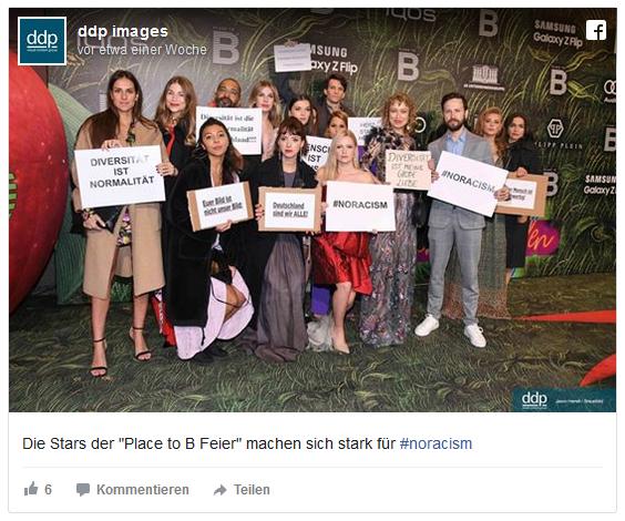 Eine Gruppe von 15 Schauspielerinnen und Schauspielern auf dem Roten Teppich der Party halten Schilder, auf denen Botschaften stehen wie NORACISM