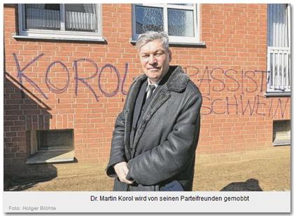 [Das Foto zeigt Martin Korol vor der beschmierten Hauswand. Die Beschriftung lautet:] Dr. Martin Korol wird von seinen Parteifreunden gemobbt