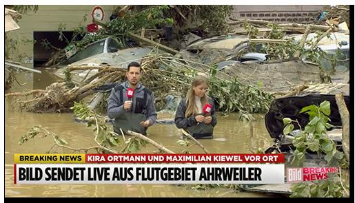 Screenshot aus einem BILD-Video: Zwei BILD-Reporter stehen bis zur Hüfte im Hochwasser, umgeben von weggeschwemmten Autos, Bäumen und Schutt
