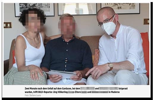 """Screenshot von BILD.de: Ein Foto von drei Personen, die auf einem Sofa sitzen; links eine Frau, in der Mitte ein Mann, der Fotos in der Hand hält, rechts ein weiterer Mann; dazu die Bildunterschrift: """"Zwei Monate nach dem Unfall auf dem Gardasee, bei dem [Name] und [Name] totgerast wurden, trifft BILD-Reporter Jörg Völkerling [Name]s Eltern [Name] und [Name] in Maderno. Foto: Stefano Laura"""""""